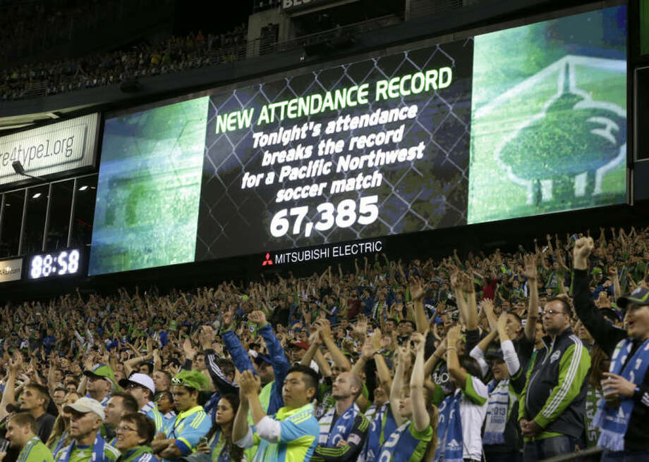 FILE - In this Aug. 25, 2013 file photo, fans cheer as a record-setting attendance of more than 67,000 is announced during a MLS soccer match between the Seattle Sounders and the Portland Timbers, in Seattle. Major League Soccer is growing, with more lucrative TV and sponsorship deals and greater attendance. But it hasn't yet translated into a television ratings breakthrough, and the league hopes the World Cup provides a long-lasting boost. (AP Photo/Ted S. Warren, File)