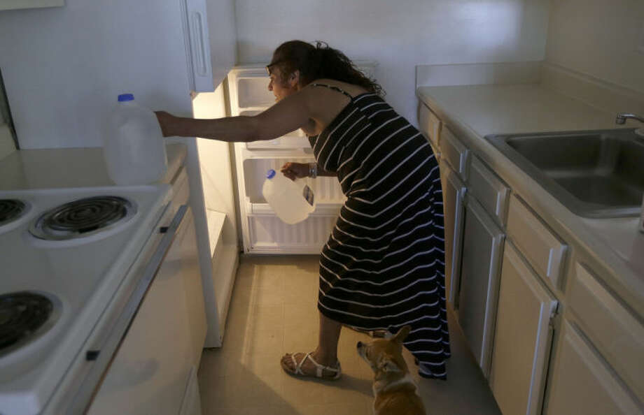 In this June 13, 2014 photo, Maria Esther Salazar loads water bottles into the refrigerator in her apartment on move-in day after living in the Jungle, a homeless encampment in San Jose, Calif. A social worker and housing specialist James Worley from nonprofit Abode Services explained that $1,295 rent will automatically be paid through a combination of public and private funds. (AP Photo/Jeff Chiu)