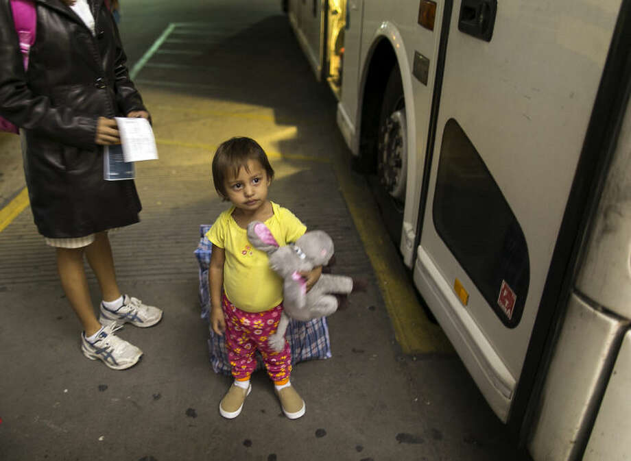 In this photo taken July 1, 2014, two-year-old Adriana Ortez holds her stuffed animal, as she and her mother, Dayana Ortez, of El Salvador, wait to board a bus leaving the city bus station in McAllen, Texas. Ortez and her daughter, were released on their own recognizance by U.S. Customs and Border Protection Services after entering the illegally into the U.S. from Mexico. The mother and daughter were heading to Los Angles to reunite with family. (AP Photo/Austin American-Statesman, Rodolfo Gonzalez)