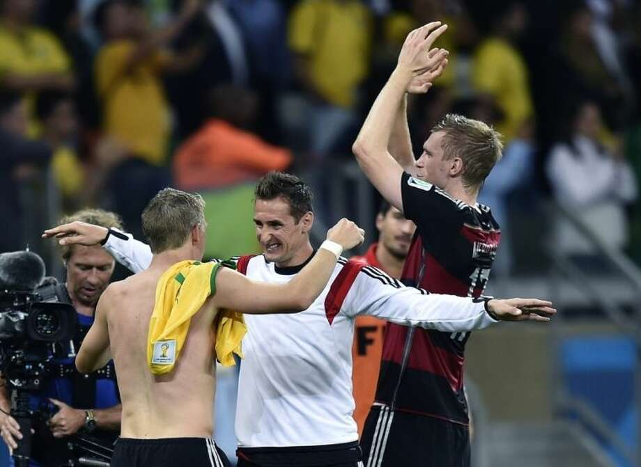 Germany's Bastian Schweinsteiger, left, and Miroslav Klose celebrate after the World Cup semifinal soccer match between Brazil and Germany at the Mineirao Stadium in Belo Horizonte, Brazil, Tuesday, July 8, 2014. Germany won the match 7-1. (AP Photo/Martin Meissner)