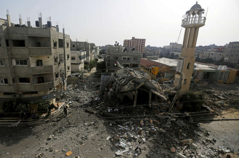 Palestinians walk around the ruins of the Al-Tawfeeq Mosque after it was hit by an overnight Israeli missile strike in the Nuseirat refugee camp, central Gaza Strip, Saturday, July 12, 2014. Israeli airstrikes targeting Hamas in Gaza hit a mosque its military says concealed the militant group's weapons, as the Palestinian death toll topped 120 Saturday in an offensive that showed no signs of slowing down. (AP Photo/Hatem Moussa)