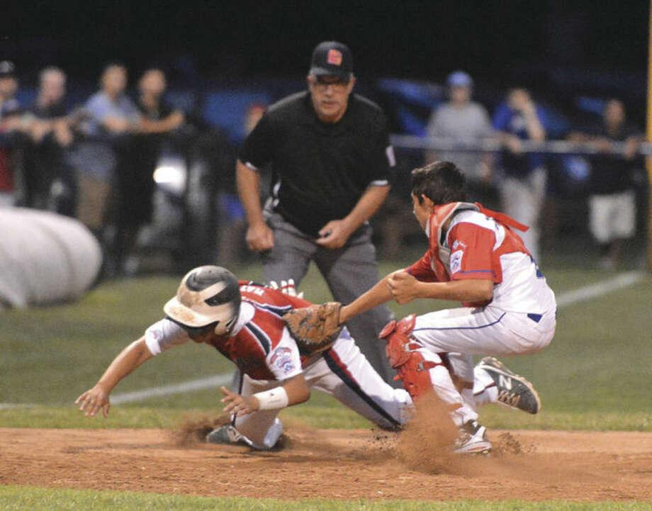 Hour photo/Alex von KleydorffNorth Stamford catcher George Psichopaidas makes the tag at third base on Norwalk's Randy Mateo during Thursday night's game.