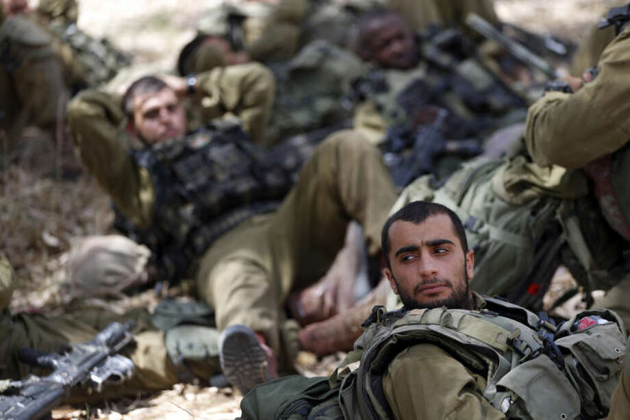 Israeli infantry soldiers rest before walking to their armored personnel carriers to move to a new position on the Israel-Gaza border, Saturday, July 12, 2014. Israeli airstrikes targeting Hamas in Gaza hit a mosque its military says concealed the militant group's weapons, as the Palestinian death toll topped 120 Saturday in an offensive that showed no signs of slowing down. Israel launched its campaign five days ago to stop relentless rocket fire on its citizens. While there have been no fatalities in Israel, Palestinian officials said overnight attacks raised the death toll there to over 120, with more than 920 wounded. (AP Photo/Lefteris Pitarakis)
