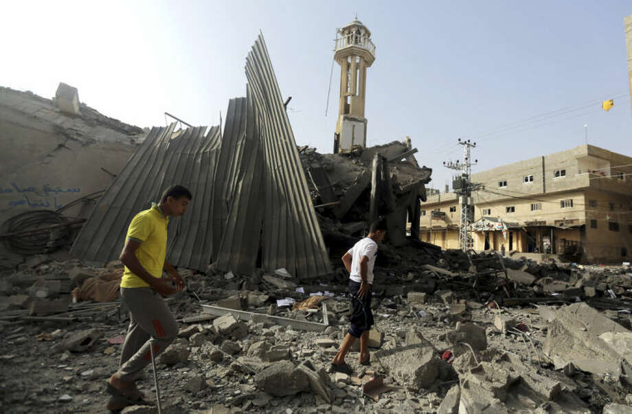 Palestinians gather around the ruins of the Al-Tawfeeq mosque after it was hit by an Israeli missile strike in the Nuseirat refugee camp, central Gaza Strip, Saturday, July 12, 2014. Israeli airstrikes overnight targeting Hamas in Gaza hit a mosque its military says concealed the militant group's weapons, as the Palestinian death toll topped 120 Saturday in an offensive that showed no signs of slowing down. (AP Photo/Hatem Moussa)