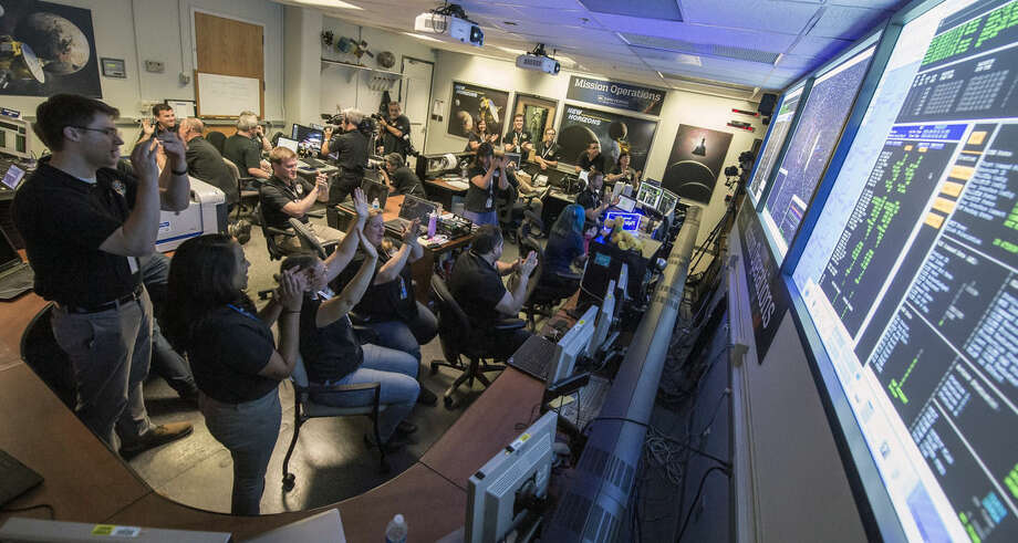 New Horizons Flight Controllers celebrate after they received confirmation from the spacecraft that it had successfully completed the flyby of Pluto, Tuesday, July 14, 2015 at the Johns Hopkins University Applied Physics Laboratory (APL) in Laurel, Md. (Bill Ingalls/NASA via AP)