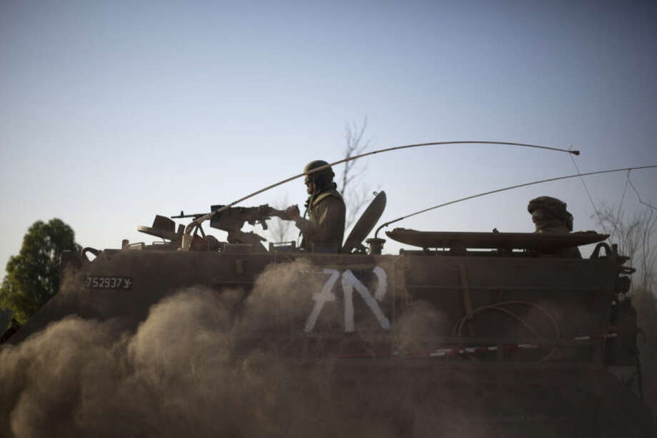 Israeli soldiers drive an armored personnel carrier to a position near the Israel Gaza border, Thursday, July 10, 2014. With rockets raining deep inside Israel, the military pummeled Palestinian targets Wednesday across the Gaza Strip and threatened a broad ground offensive, while the first diplomatic efforts to end two days of heavy fighting got underway. Egypt, which has mediated before between Israel and the Hamas militant group, said it spoke to all sides about ending the violence. U.S. Secretary of State John Kerry was in touch with Israel to try to lower tensions. And the United Nations chief warned of a