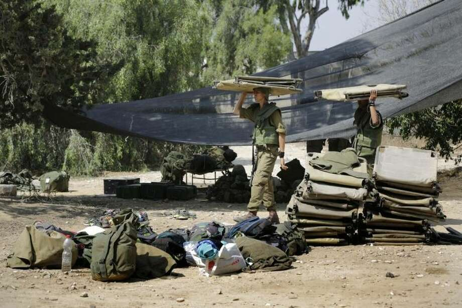 Israeli soldiers carry a bunk beds near the Israel Gaza border, Israel, Monday, July 7, 2014. The Islamic militant group Hamas that rules Gaza vowed revenge on Israel for the death of several of its members killed in an airstrike early Monday morning in the deadliest exchange of fire since the latest round of attacks began weeks ago. (AP Photo/Tsafrir Abayov)