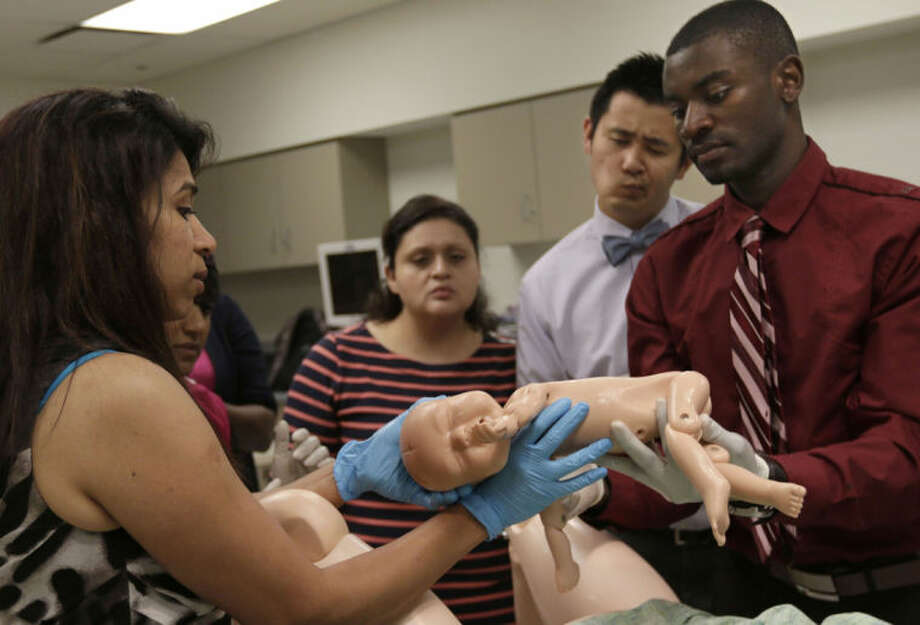 In this June 25, 2014 photo, interns gather around during an intern boot camp exercise taught by both Northwestern Memorial Hospital and Northwestern University's Feinberg School of Medicine in Chicago. (AP Photo/Stacy Thacker)