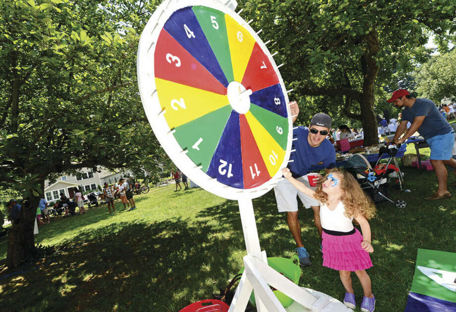 Hour photo / Erik Trautmann Ruby Harder, 3, tries her hand at the lucky wheel with the help of her dad, Bryn Harder, during the 45th annual Rowayton Civic Association River Ramble! at Pinkney Park Saturday.