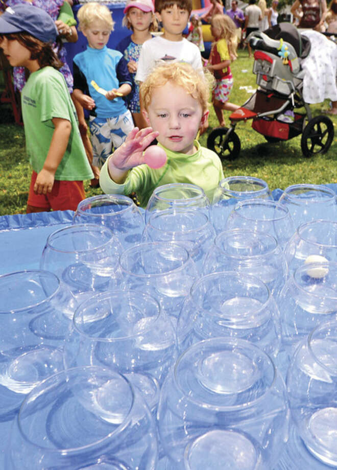 Hour photo / Erik Trautmann 3 year old Palmer Bowen tries his hand at the goldfish toss during the 45th annual Rowayton Civic Association River Ramble! at Pinkney Park Saturday.