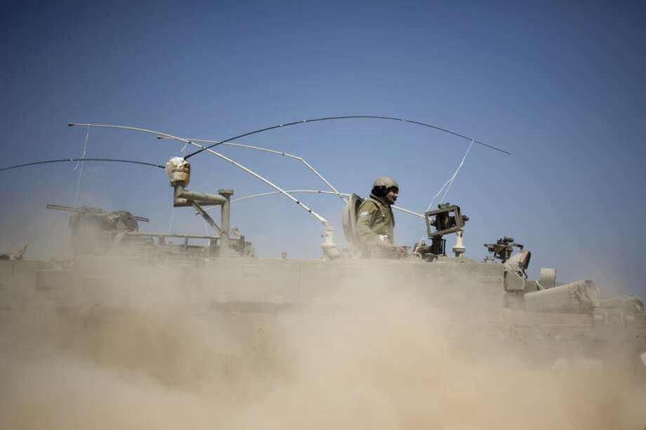 Israeli soldiers drive on an armored personnel carrier near the Israel and Gaza Strip border, Monday, July 7, 2014. The Islamic militant group Hamas that rules Gaza vowed revenge on Israel for the death of several of its members killed in an airstrike early Monday morning in the deadliest exchange of fire since the latest round of attacks began weeks ago. About a dozen rockets were fired at Israel from Gaza overnight the military said. (AP Photo/Ariel Schalit)