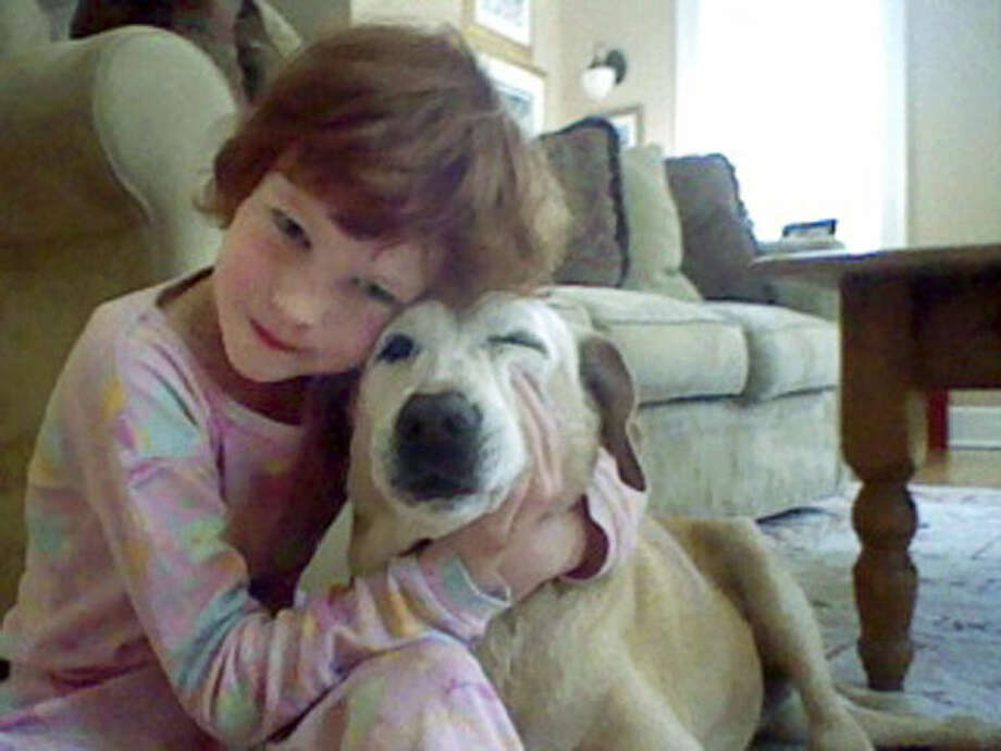In this April 2012 photo provided by Jenny Hubbard, her daughter Catherine Hubbard hugs their dog Sammy at their home in Newtown, Conn. Despite her tragic death in the mass shooting at Sandy Hook Elementary School on Dec. 14, 2012, Catherine's dream of helping animals is close to becoming a reality. By early August 2014, the state is expected to finalize transferring 34.4 acres of the former Fairfield Hills Hospital in Newtown to the Catherine Violet Hubbard Foundation Inc., which is raising money to fund the new Catherine Violet Hubbard Animal Sanctuary. (AP Photo/Jenny Hubbard)