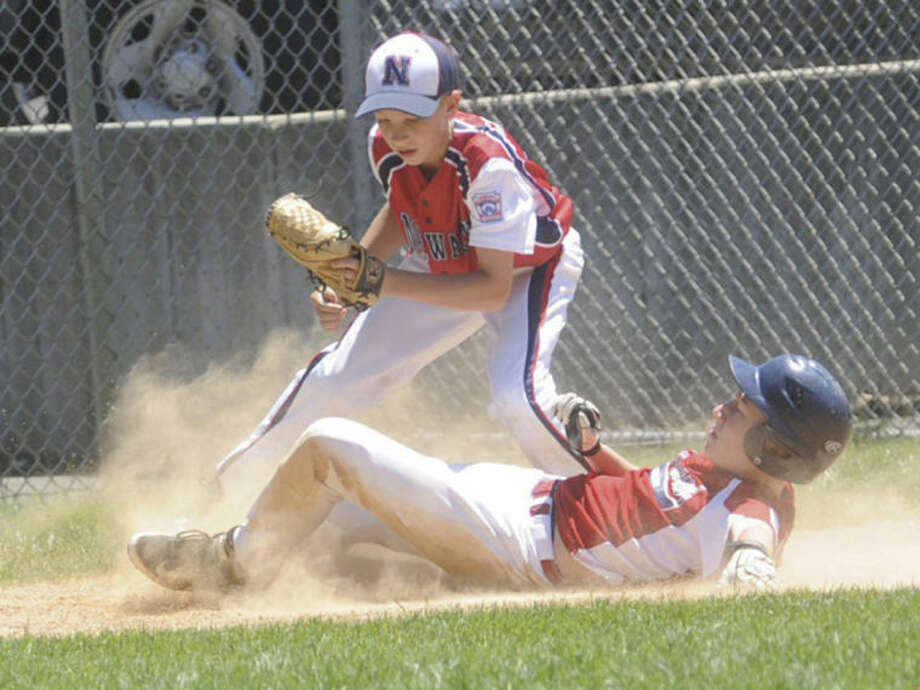 Hour photo/Matthew VinciNorwalk's Jack Fitzpatrick, top, tags out Stamford American's Evan Campbell at third base during Sunday's District 1 Little League tournament game in Darien.