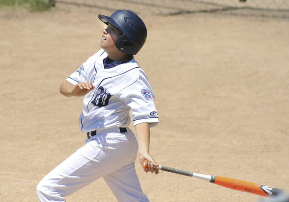Hour photo/John Nash - Kyle Hyzy of Wilton watches his grand slam head toward the outfield during Sunday's District 1 Little League game in Darien. Wilton defeated Darien National 29-2. Hyzy was 4-for-4 with two home runs and 8 RBIs.