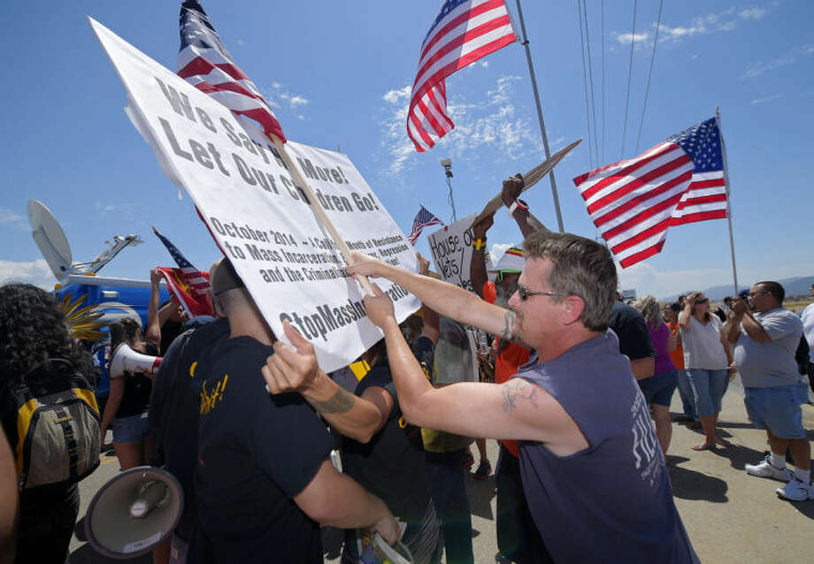 Demonstrators shove each other, Friday, July 4, 2014, outside a U.S. Border Patrol station in Murrieta, Calif. Demonstrators on both sides of the immigration debate had gathered where the agency was foiled earlier this week in an attempt to bus in and process some of the immigrants who have flooded the Texas border with Mexico. (AP Photo/Mark J. Terrill)
