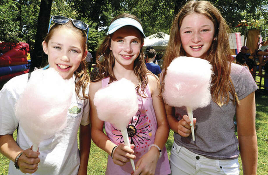 Hour photo / Erik Trautmann Meghan Sisk, Katherine Klein, and Katherin Sidolph enjoy a cotton candy during the 45th annual Rowayton Civic Association River Ramble! at Pinkney Park Saturday.