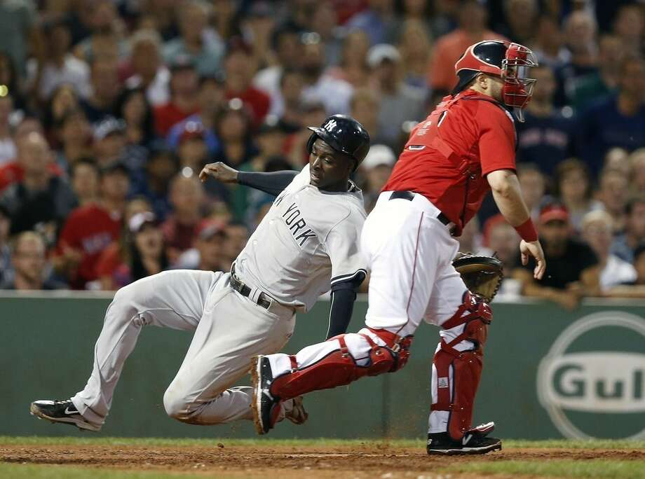 New York Yankees' Didi Gregorius, left, scores on a single by Jacoby Ellsbury as Boston Red Sox's Sandy Leon, right, looks for the throw during the eighth inning of a baseball game in Boston, Friday, July 10, 2015. (AP Photo/Michael Dwyer)