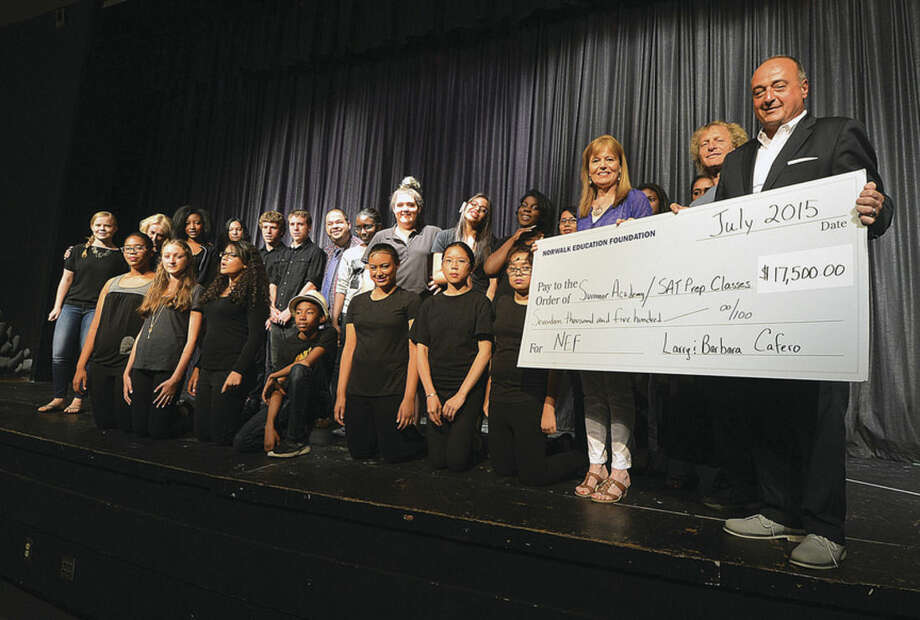 Hour Photo/Alex von Kleydorff Larry and Barbara Cafero joined by students with the Crystal Theater and School of Rock present a check to the Norwalk Education Foundation for the Summer Academy Program