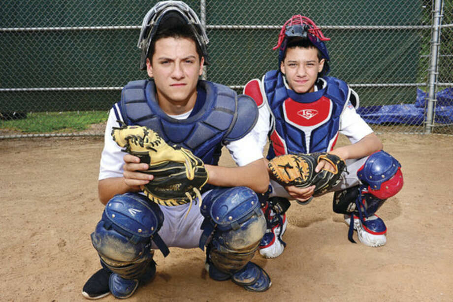 Hour photo/Erik TrautmannHunter Dumas, left, who plays catcher on the Norwalk Babe Ruth 15-year-old all-star team, and his little brother, Jake Dumas, who also plays catcher for Norwalk's 12-year-old Little League All-Stars.