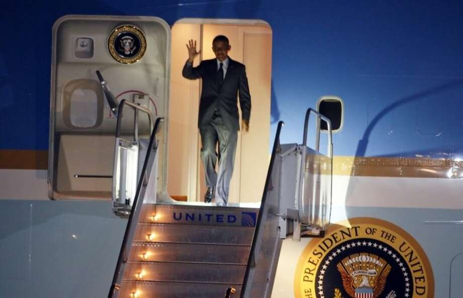 President Barack Obama waves as he exits Air Force One on arrival to Austin-Bergstrom International Airport on Wednesday, July 9, 2014, in Austin, Texas. Obama is spending the night in the Texas capital and on Thursday he will make a speech on the economy. (AP Photo/Jack Plunkett)