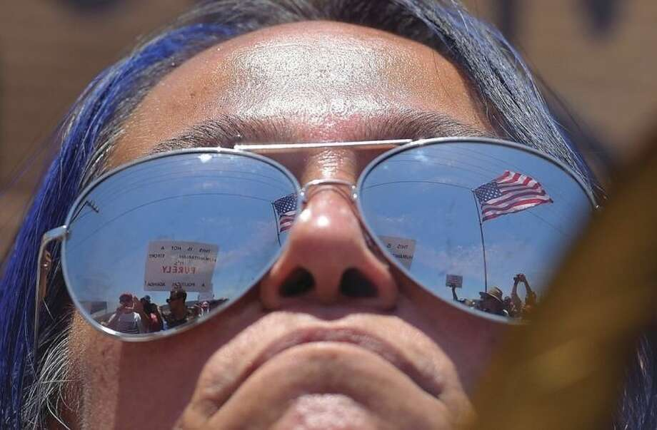 AP photo/Mark J. TerrillA pro-immigration demonstrator looks across a police line at the opposing side, Friday, July 4, outside a U.S. Border Patrol station in Murrieta, Calif.