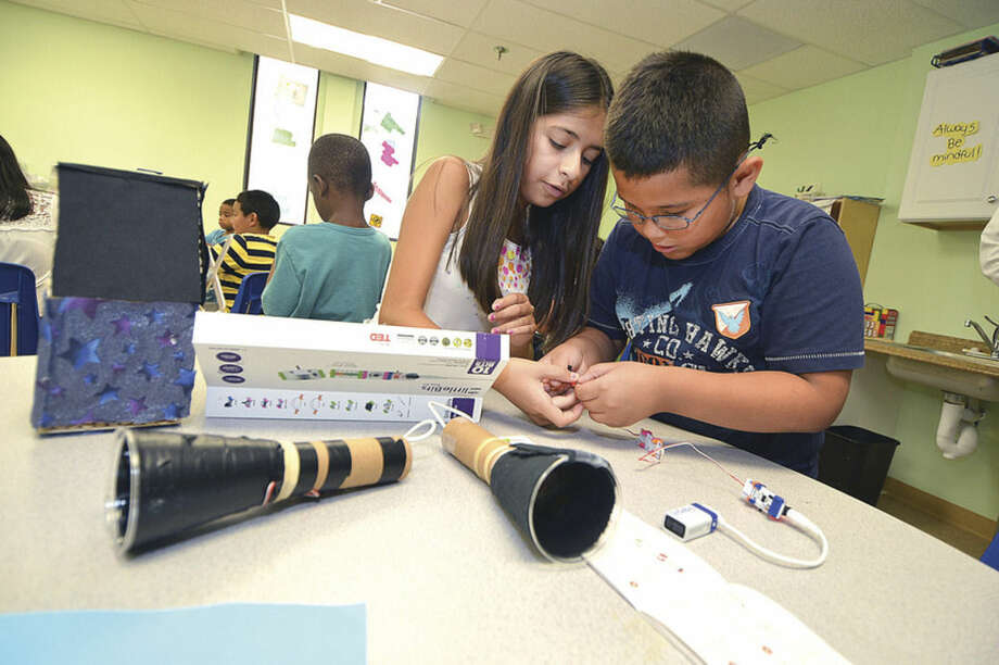 Hour photo/Alex von KleydorffTrisha Lopez and Marvin Lopez connect the electronics for the flashlights they are making in the Learning for Life summer enrichment program at SoNo Community Center.