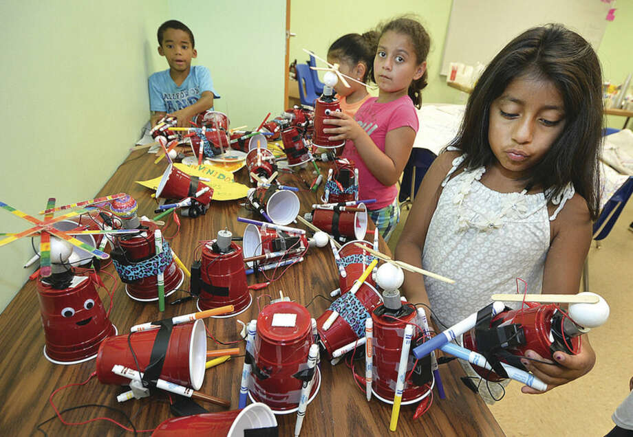 Hour photo/Alex von KleydorffAngie Aguilar picks an Art-Bot from the ones they made in the Learning for Life summer enrichment program at the SoNo Community Center.