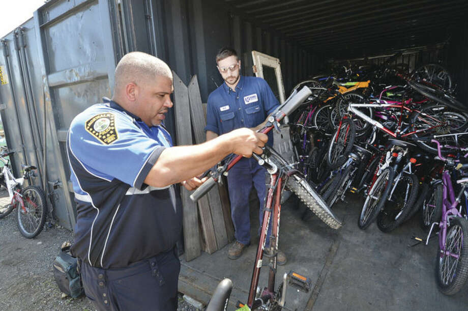 Hour Photo/Alex von Kleydorff Norwalk Police Officer Hector Delgado passes a bike to Rick Lindstrom after marking it with a reference number for the Two Wheels Organization