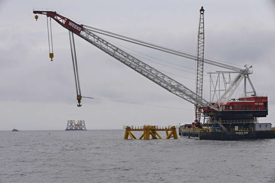The first foundation jacket installed by Deepwater Wind in the nation's first offshore wind farm construction project is seen next to a construction crane Monday, July 27, 2015, on the waters of the Atlantic Ocean off Block Island, R.I. Other foundation jackets and a deck yet to be installed our seen on a barge behind the crane. Deepwater Wind will consist of five turbines producing a total of 30 megawatts of electricity. (AP Photo/Stephan Savoia)