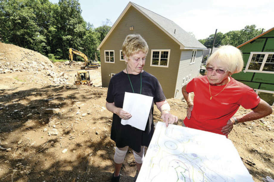 Hour photo / Erik Trautmann Rolling Ridge condominium residents Emy Jane Jones and Sally Dodd are up in arms over plans to build four duplexes at 69 Aiken St.