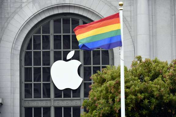 A pride flag flies near signage displayed outside the Bill Graham Civic Auditorium ahead of the Apple World Wide Developers Conference (WWDC) in San Francisco, California, U.S., on Monday, June 13, 2016. Apple Inc. has lost ground to Alphabet Inc.'s Google in the hot voice-activated assistant space. By releasing a software kit at today's Worldwide Developers Conference that lets programmers integrate Siri into their apps, it hopes to catch up with the maker of Google Now and the Android operating system -- as well as Amazon.com Inc.'s Alexa virtual helper -- and thus tie customers more closely to its iOS system. Photographer: Michael Short/Bloomberg