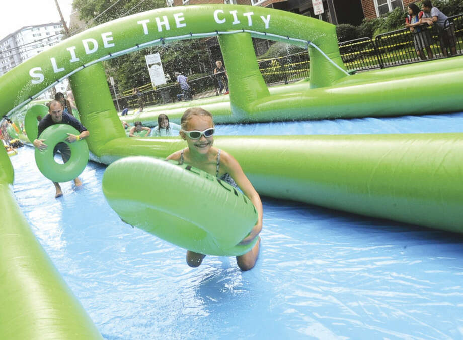 Samantha Fenny 10, on the giant water slide at the Slide City event held in downtown Stamford. Hour photo/Matthew Vinci