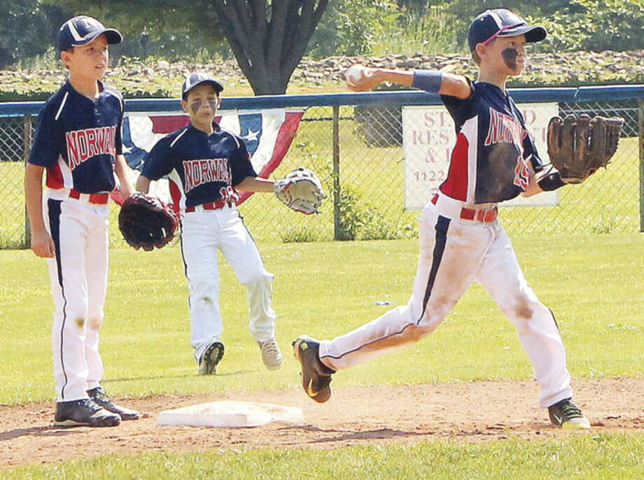Hour photo/Joe RyanNorwalk Little League 10-year-old All-Star second baseman Alistair Morin, right, fires to first after forcing a runner at second base as teammates Javier Gonzalez, left, and Jose Vasquez look on during a District 1 game in Stamford.