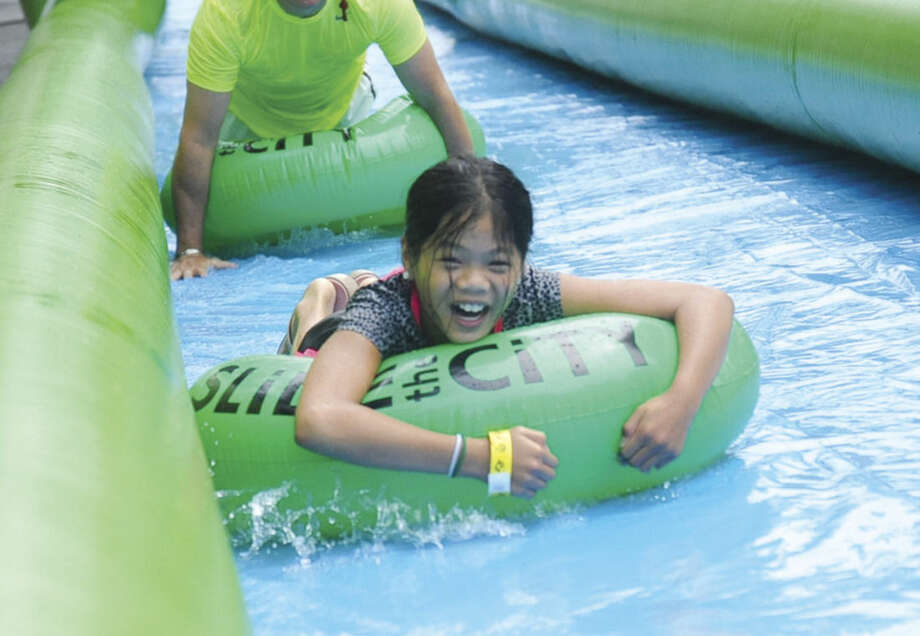 Hour photo/Matthew VinciMichelle Ferone, 10, heading to the bottom of the giant water slide at the Slide City event held in downtown Stamford.