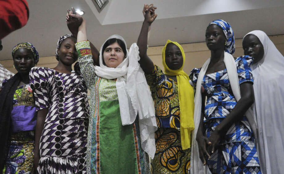 Pakistani activist Malala Yousafzai, centre, raises her hands with some of the escaped kidnapped school girls of government secondary school Chibok during a news confrence, in Abuja, Nigeria, Monday, July 14, 2014. Yousafzai on Monday won a promise from Nigeria's leader to meet with the parents of some of the 219 schoolgirls held by Islamic extremists for three months. Malala celebrated her 17th birthday on Monday in Nigeria with promises to work for the release of the girls from the Boko Haram movement. (AP Photo/Olamikan Gbemiga)