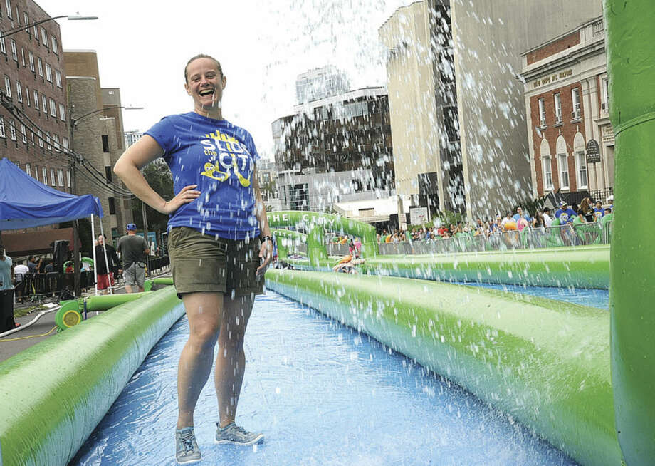 Volunteer Charity Miller gets wet Sunday on the giant water slide at the Slide City event held in downtown Stamford. Hour photo/Matthew Vinci