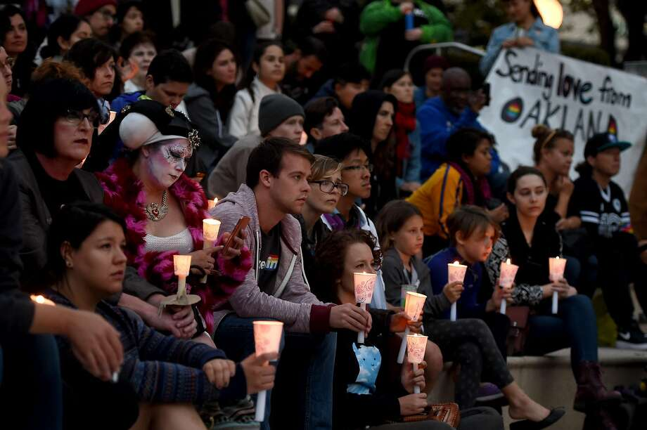 Victims of the Orlando shooting are honored and remembered during an Oakland Out for Orlando community Vigil held at city hall in Oakland, Calif., on Sunday, June 12, 2016. The vigil was held for victims of the Orlando, Fla. nightclub shooting which killed at least 50 people and was the deadliest U.S. mass shooting to date. (Susan Tripp Pollard/Oakland Tribune via AP) Photo: JANE TYSKA, Associated Press