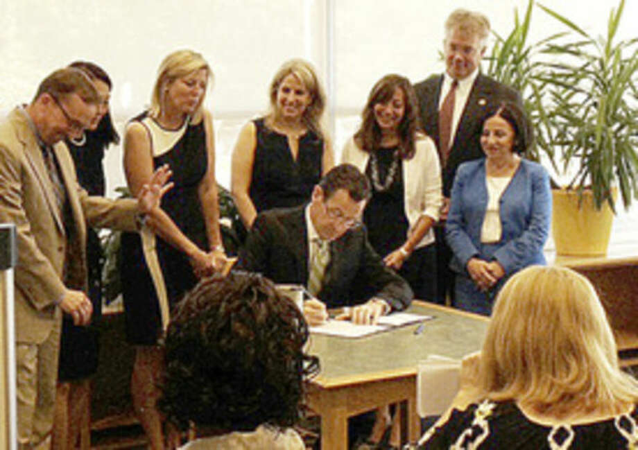 Photo by Meaghan LatellaGov. Dannel Malloy signs a new state law that allows trained school employees to administer the life-saving treatment epipenphrine in Weston on Monday.
