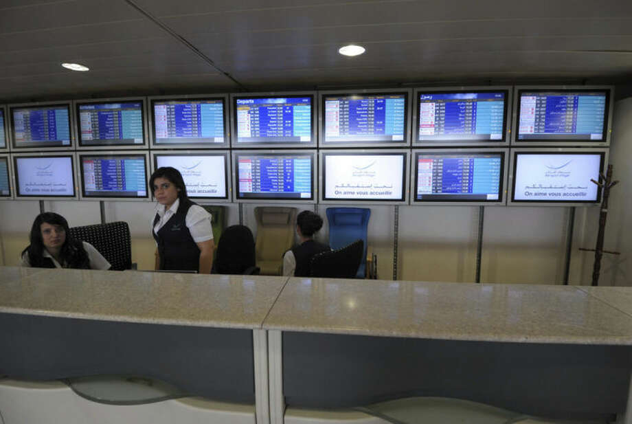 """Air Algerie ground attendants sit behind their desk next to arrival and departure information screens at the Houari Boumediene airport near Algiers, Algeria, Thursday, July 24, 2014. An Air Algerie flight carrying 116 people from Burkina Faso to Algeria's capital disappeared from radar early Thursday over northern Mali and """"probably crashed"""" according to the plane's owner and government officials in France and Burkina Faso. (AP Photo/Sidali Djarboub)"""