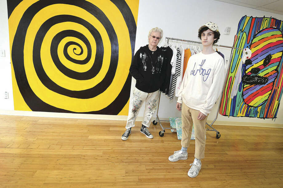 Hour Photo/Alex von KleydorffFrank Foster Post and son Philip Post stand in front of the two murals Frank painted in his son's store, Dertbag, in Bridgeport's Arcade shops.