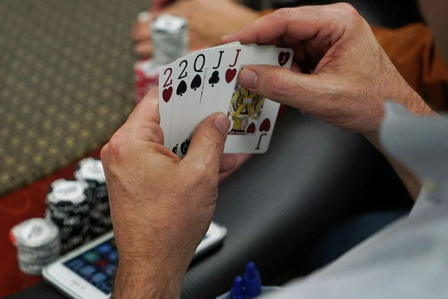 Scott Slinker plays a game of poker at his office in San Jose, Calif., on April 13, 2016. Slinker hosts poker night where him and his friends talk about things such as politics. Photo: James Tensuan /For The San Francisco Chronicle / James Tensuan