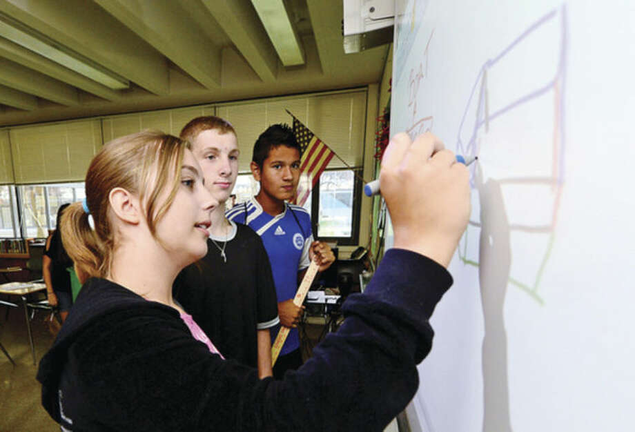 Hour photo / Erik Trautmann Wiktoria Piktl, Chris Buzzeo and Chris Vega work on the plans for their final project during the Norwalk Public Schools and Carver Center Freshman Summer Academy for incoming freshman at Norwalk High School Wednesday.