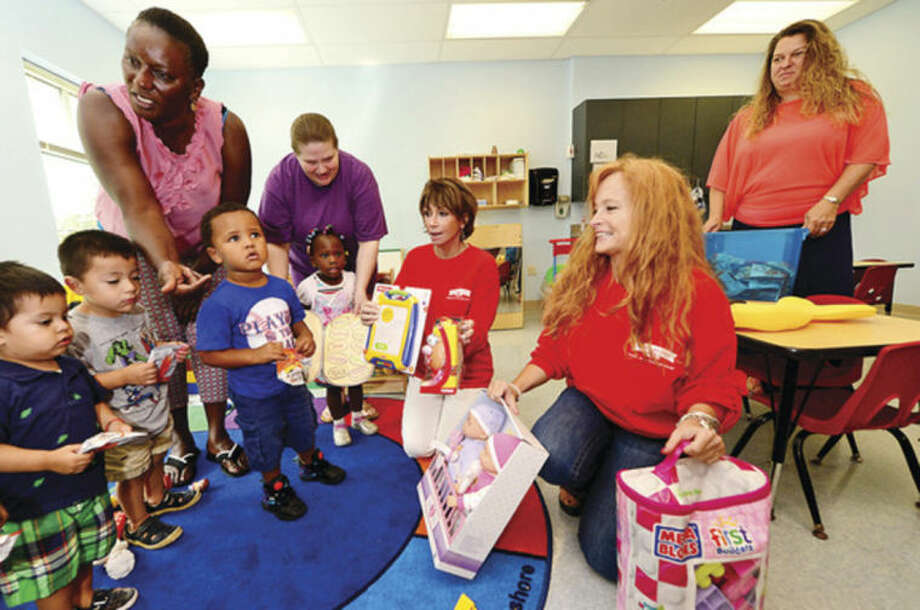 Hour photo/Erik TrautmannRuth Ann Walsh, center, and Carol Lamont of Pepperidge Farm donate nearly 500 toys and learning materials to the Head Start program at Nathaniel Ely School in Norwalk Thursday.