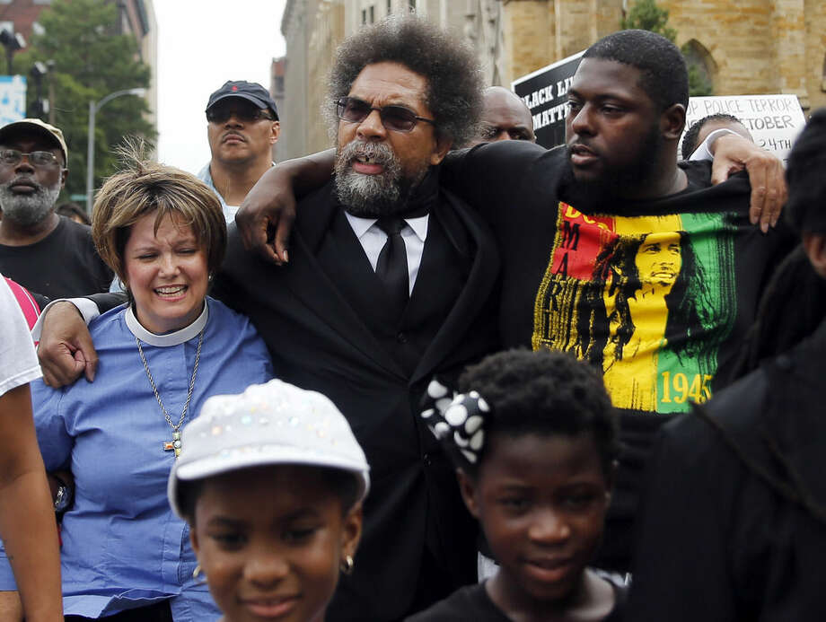 Cornel West, center, flanked by activists Tory Wilson, right, and the Rev. Renita Lamkin, left, march to the Thomas F. Eagleton Federal Courthouse, Monday, Aug. 10, 2015, in St. Louis. Several protesters were arrested at the courthouse. (AP Photo/Jeff Roberson)