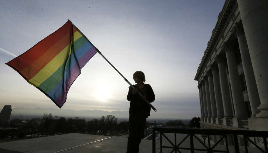 FILE - In this Jan. 28, 2014 file photo, Corbin Aoyagi, a supporter of gay marriage, waves a rainbow flag during a rally at the Utah State Capitol in Salt Lake City. On Tuesday, Aug. 5, 2014, the state of Utah asked the U.S. Supreme Court to uphold the state's gay marriage ban. The ban was ruled unconstitutional by a federal judge and later a federal appellate court. This is Utah's last chance for a court to say its ban is legal. (AP Photo/Rick Bowmer, File) (AP Photo/Rick Bowmer, File)
