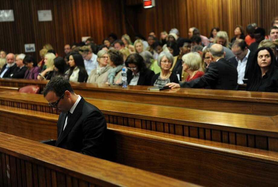 Oscar Pistorius sits in court as his murder trial resumes, in Pretoria, South Africa, Thursday, Aug. 7 2014. The chief prosecutor in Oscar Pistorius' murder trial said Thursday the double-amputee athlete's lawyers have floated more than one theory in a dishonest attempt to defend against a murder charge for his killing of girlfriend Reeva Steenkamp. (AP Photo/Werner Beukes, Pool)