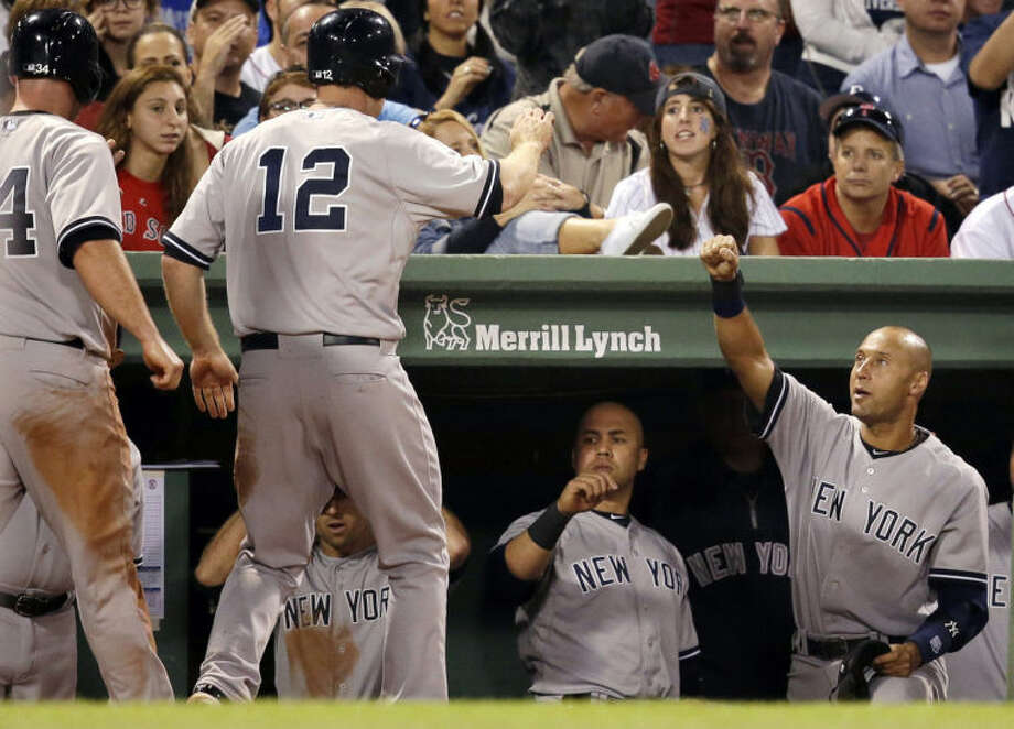 New York Yankees' Derek Jeter, right, greets teammates Brian McCann, left, and Chase Headley (12), into the dugout after they both scored on a single by Yankees' Stephen Drew in the fifth inning of a baseball game against the Boston Red Sox, in Boston, Sunday, Aug. 3, 2014. (AP Photo/Steven Senne)
