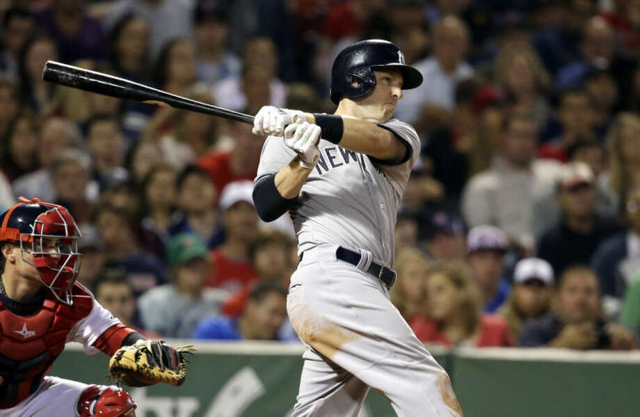 New York Yankees' Stephen Drew hits a two-run single as Boston Red Sox catcher Christian Vazquez, left, looks on in the fifth inning of a baseball game, in Boston, Sunday, Aug. 3, 2014. (AP Photo/Steven Senne)