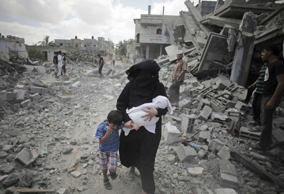A Palestinian woman passes by rescuers inspecting the rubble of destroyed houses following Israeli strikes in Rafah refugee camp, southern Gaza Strip, Monday, Aug. 4, 2014. (AP Photo/Khalil Hamra)