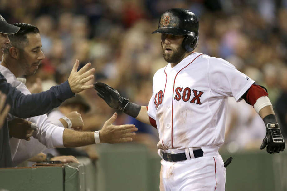 Boston Red Sox's Dustin Pedroia, right, is welcomed to the dugout after hitting a two-run home run in the second inning of a baseball game against the New York Yankees, in Boston, Sunday, Aug. 3, 2014. (AP Photo/Steven Senne)